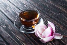 Чашка магнолии черного чая и цветка на деревянных досках Стоковые Изображения RF