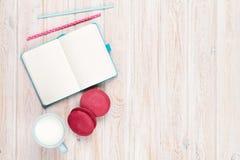 Чашка молока и macarons на белом деревянном столе с блокнотом Стоковая Фотография RF