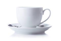 Чашка на поддоннике с ложкой на белой предпосылке Стоковая Фотография RF