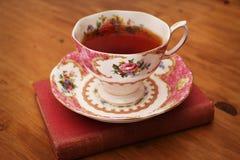 Чашка розового чая и книга 2 антиквариата Стоковые Фотографии RF