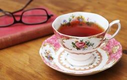 Чашка розового чая и книга 2 антиквариата Стоковые Фото