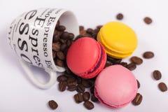 Чашка с кофейными зернами с красочными очень вкусными французскими macaroons на белом конце предпосылки вверх Стоковые Изображения
