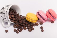 Чашка с кофейными зернами с красочными очень вкусными французскими macaroons на белом конце предпосылки вверх Стоковое Изображение RF