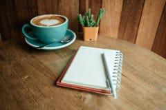 Чашка с кофе имеет форму сердца на тетради верхней части и дневника с Стоковое фото RF