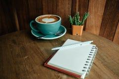 Чашка с кофе имеет форму сердца на тетради верхней части и дневника с Стоковое Фото