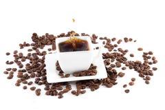 Чашка с кофе, кофейные зерна и кофе брызгают Стоковое фото RF