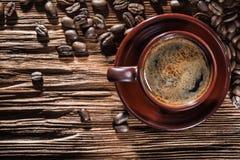 Чашка с кофе на винтажной деревянной доске и фасолях стоковая фотография
