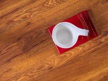 Чашка с поддонником на таблице Стоковые Изображения