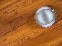 Чашка с поддонником на таблице Стоковое Изображение