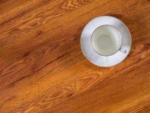 Чашка с поддонником на таблице Стоковое Изображение RF
