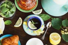 Чашка травяного чая с листьями лимона и мяты, корнем имбиря и круассаном Стоковая Фотография RF