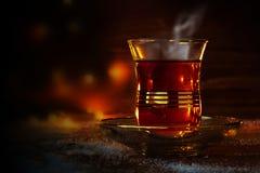 Чашка турецкого чая на поддоннике на деревенской древесине с снегом перед темнотой запачкала предпосылку с красными и золотыми св Стоковая Фотография RF