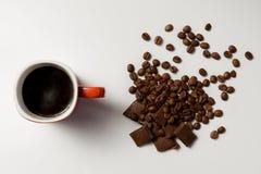 Чашка душистых кофе, фасолей кофе и шоколада на белой предпосылке Стоковые Фотографии RF