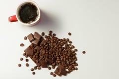 Чашка душистых кофе, фасолей кофе и шоколада на белой предпосылке Стоковое фото RF