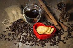 Чашка формы сердца, хлеб в красных кофейных зернах сердца и на деревянном Стоковые Изображения