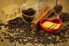 Чашка формы сердца, хлеб в красных кофейных зернах сердца и на деревянном Стоковые Фото