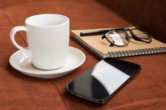 Чашка, чашка кофе и smartphone с примечанием дневника на красном ковре o Стоковое Фото