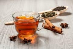 Чашка чаю, 2 деревянных ложки с листьями зеленого и черного чая Стоковое Изображение
