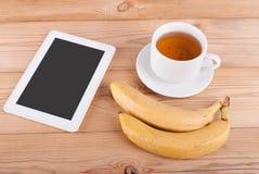 Чашка чаю и бананы таблетки цифров Стоковые Изображения RF