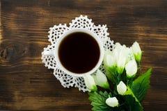 Чашка чаю и белые тюльпаны на деревянной предпосылке Букет желтых тюльпанов и чашки кофе Стоковое фото RF
