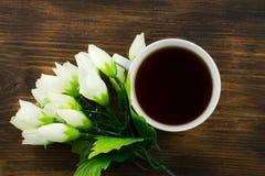 Чашка чаю и белые тюльпаны на деревянной предпосылке Букет желтых тюльпанов и чашки кофе Стоковые Изображения