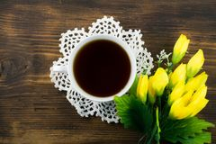 Чашка чаю и желтые тюльпаны на деревянной предпосылке Букет желтых тюльпанов и чашки кофе Стоковые Изображения RF