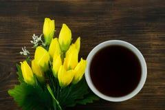 Чашка чаю и желтые тюльпаны на деревянной предпосылке Букет желтых тюльпанов и чашки кофе Стоковые Изображения