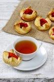 Чашка чаю и малые торты на деревянной деревенской таблице стоковое изображение rf