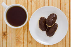 Чашка чаю и мини eclairs Стоковое Изображение RF