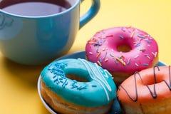 Чашка чаю и плита с donuts в поливе на оранжевой предпосылке Стоковые Фотографии RF
