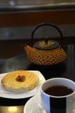 Чашка чаю и чайник на черной предпосылке Стоковая Фотография