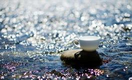 Чашка чаю, кофе, какао в воде на аисте на каменистом d стоковое фото rf