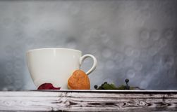 Чашка чаю на деревянном столе с яркими листьями осени и печеньями сердца против стоковое фото