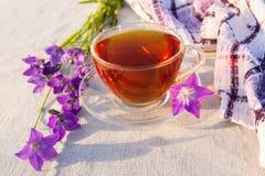 Чашка чаю на checkered салфетке и голубых цветках колокола Стоковая Фотография