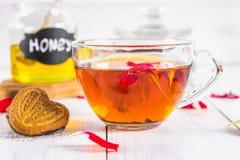 Чашка чаю, печенья, на заднем плане чонсервной банкы меда и бака черного травяного флористического чая на белом деревянном столе Стоковая Фотография