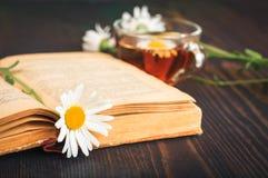 Чашка чаю, стоцвет и книга на таблице стоковые изображения