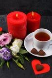 Чашка чаю с букетом роз и свечей, конфеты на сердце на каменной предпосылке Взгляд сверху от угла Стоковое Фото