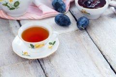 Чашка чаю с вареньем ягоды и свежие фрукты на старом деревянном столе Стоковые Изображения RF