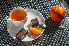Чашка чаю с вафлями в шоколаде с печеньями и апельсином стоковые изображения