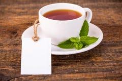 Чашка чаю с листьями зеленого цвета и белой биркой Стоковое Изображение RF