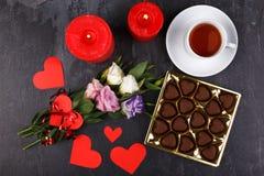 Чашка чаю с коробкой шоколадов и свечей на каменной предпосылке над взглядом Стоковая Фотография