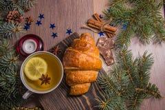 Чашка чаю с круассаном на деревянной предпосылке с оформлением ` s Нового Года стоковые изображения rf