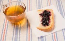 Чашка чаю с куском хлеба с вареньем на ткани таблицы Стоковые Изображения RF