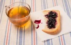 Чашка чаю с куском хлеба с вареньем на ткани таблицы Стоковые Изображения