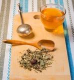 Чашка чаю с кучей сухих трав на деревянном столе Стоковые Изображения RF