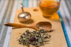 Чашка чаю с кучей сухих трав на деревянном столе Стоковая Фотография
