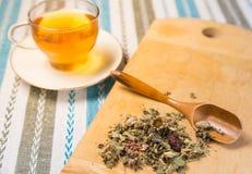 Чашка чаю с кучей сухих трав на деревянном столе Стоковые Изображения