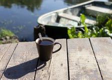 Чашка чаю с ложкой на деревянных предпосылке, реке и шлюпке позади стоковое фото