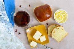 Чашка чаю с мягкой плюшкой, маслом, кусками лимона хороший старт к дню Стоковое Фото