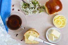 Чашка чаю с мягкой плюшкой, маслом, кусками лимона хороший старт к дню стоковые изображения rf